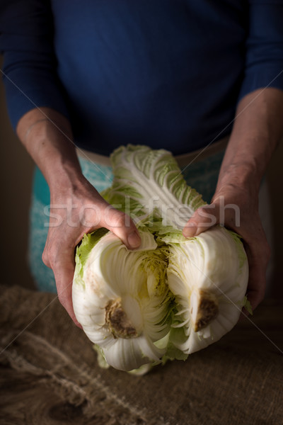 Woman shares the Chinese cabbage into two halves on the table Stock photo © Karpenkovdenis