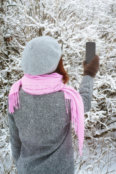 Woman takes pictures of the winter  trees vertical Stock photo © Karpenkovdenis