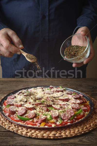 Man sprinkle with spice pizza from a glass sauser Stock photo © Karpenkovdenis