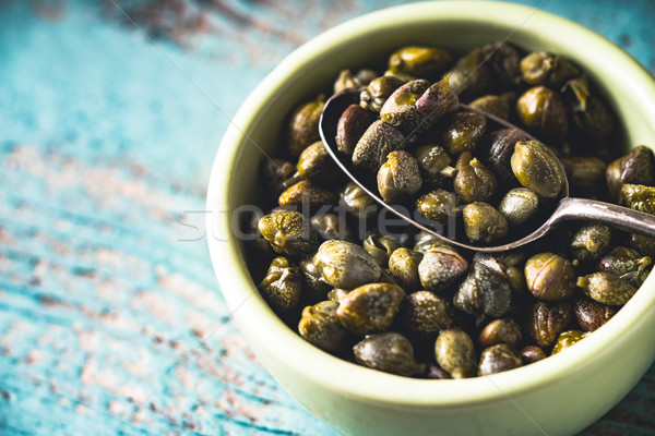 Capers in the bowl on the light blue background Stock photo © Karpenkovdenis