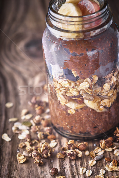Chocolate chia pudding with oat flakes in the glass jar on the wooden table Stock photo © Karpenkovdenis
