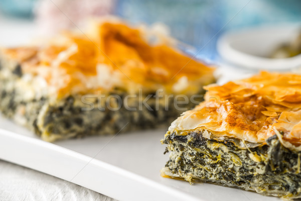 Greek pie spanakopita on the white plate with blurred accessorizes horizontal Stock photo © Karpenkovdenis