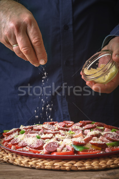 Man in a blue shirt sprinkle with cheese pizza from a sauser Stock photo © Karpenkovdenis