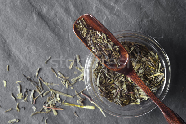 Glass jar with tea and wooden spoon on the dark stone background top view Stock photo © Karpenkovdenis