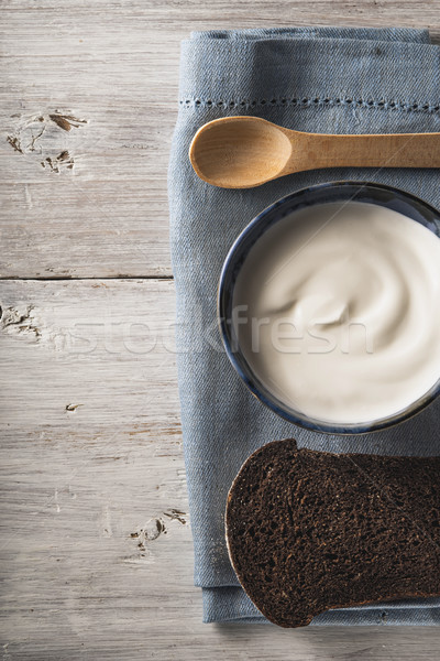 Sour cream on the ceramic dish with bread on the white wooden table vertical Stock photo © Karpenkovdenis