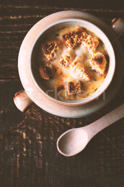 Onion soup in the ceramic pot  with spoon on the wooden table vertical Stock photo © Karpenkovdenis