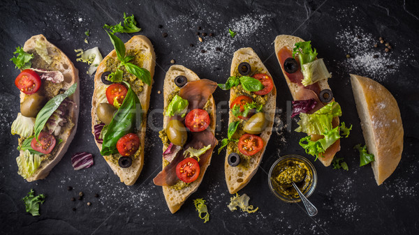 Slices of ciabatta with olives , tomatoes and basil on the black stone table wide screen Stock photo © Karpenkovdenis