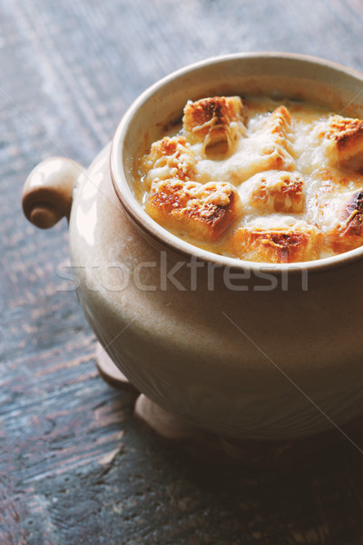 Onion soup in the ceramic pot on the wooden table vertical Stock photo © Karpenkovdenis
