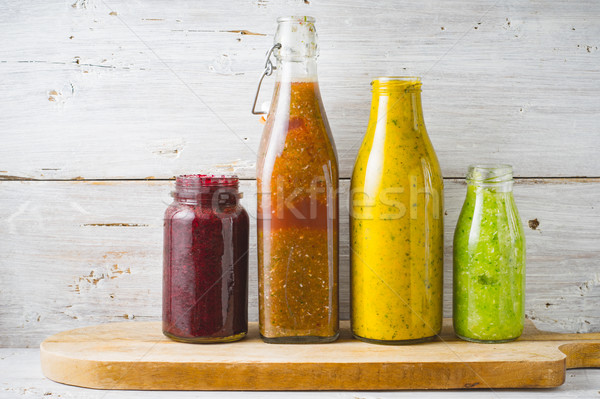 Bottles and jar with different smoothie on the white wooden background horizontal Stock photo © Karpenkovdenis