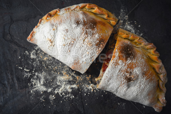 Sliced calzone with flour on the dark stone background top view Stock photo © Karpenkovdenis