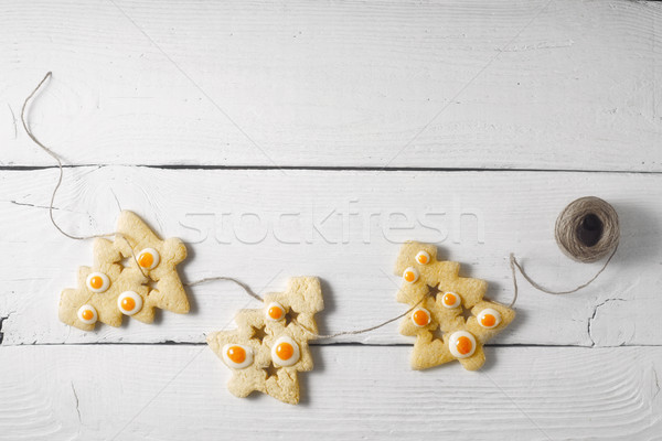 Garland of Christmas cookies on the white wooden background top view Stock photo © Karpenkovdenis