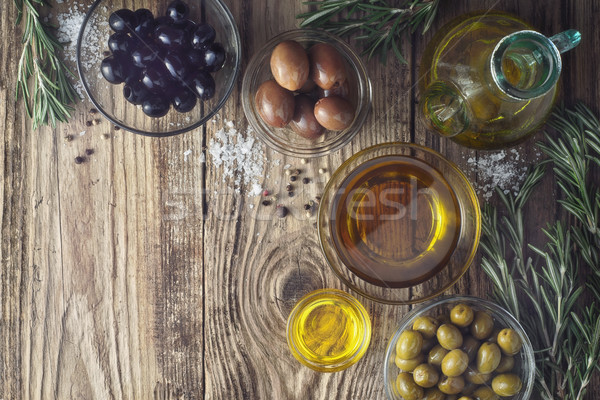 Olives with olive oil and rosemary on the wooden table top view Stock photo © Karpenkovdenis