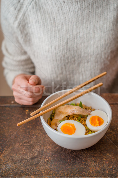 Stock photo: Woman behind the table and the Asian soup Ramen