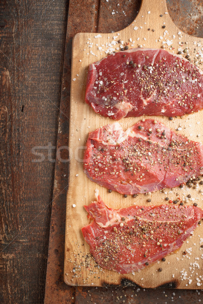 Raw beef steak and spicel on cutting board on the table Stock photo © Karpenkovdenis