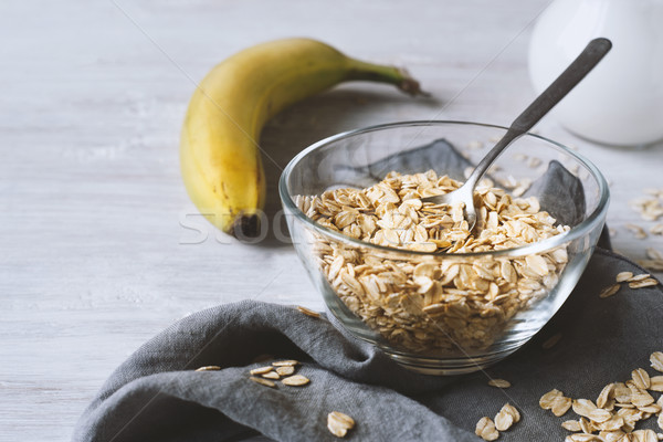 Oat flakes in a glass bowl and banana on the wooden table Stock photo © Karpenkovdenis