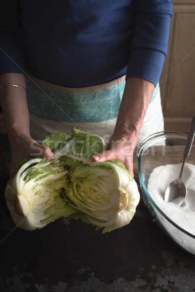 Woman Chinese cabbage divided into two halves for making kimchi Stock photo © Karpenkovdenis