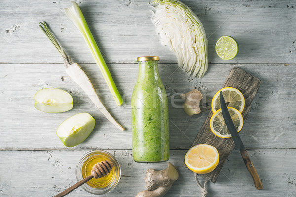 Glass bottle with vegetable smoothie with different ingredient on the white wooden table top view Stock photo © Karpenkovdenis