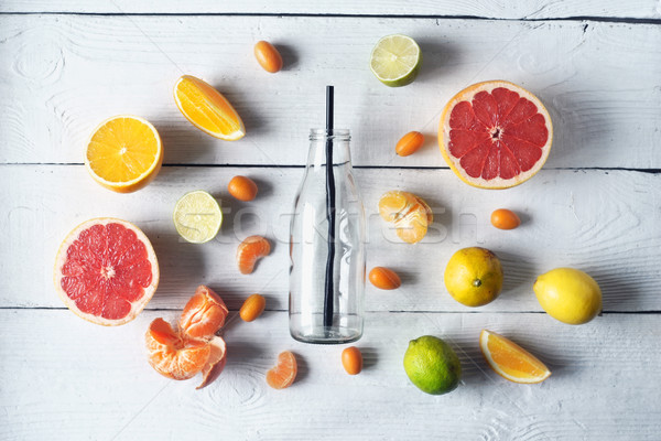 Glass bottle surrounded by different citrus on the white wooden table top view Stock photo © Karpenkovdenis