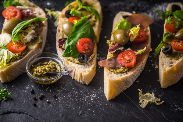 Slices of ciabatta with olives , tomatoes and basil on the black stone table Stock photo © Karpenkovdenis