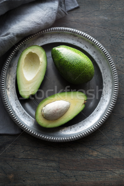 Avocado in the metal plate on the dark scratched table vertical Stock photo © Karpenkovdenis