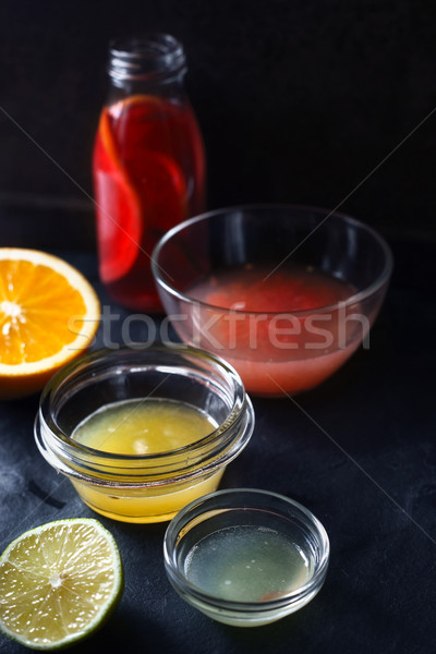 Citrus juice in the different glass bowl on the dark stone background Stock photo © Karpenkovdenis