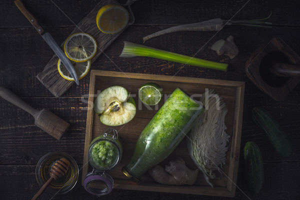 Stock photo: Bottle and jar with smoothie in the wooden tray  with different ingredients on the wooden table