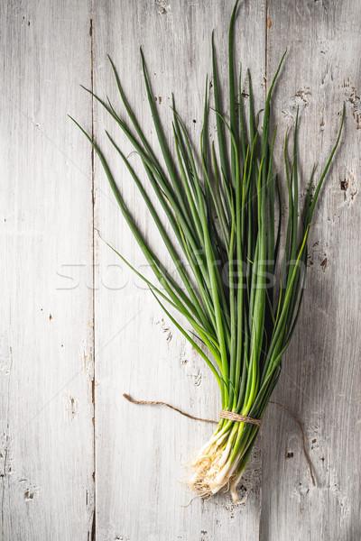 Green onion on the white wooden table top view Stock photo © Karpenkovdenis