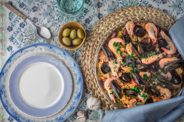 Paella on the metal plate on the beautiful napkin with tableware top view Stock photo © Karpenkovdenis