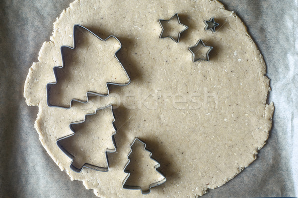 Christmas cookie cutters on the raw dough on the parchment top view Stock photo © Karpenkovdenis