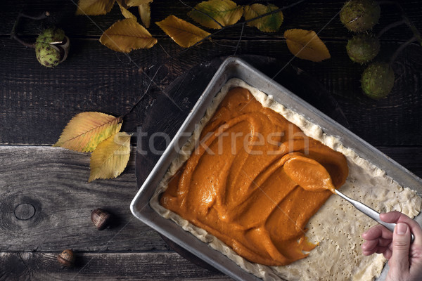 Putting spicy pumpkin puree on the dough for pumpkin pie top view Stock photo © Karpenkovdenis