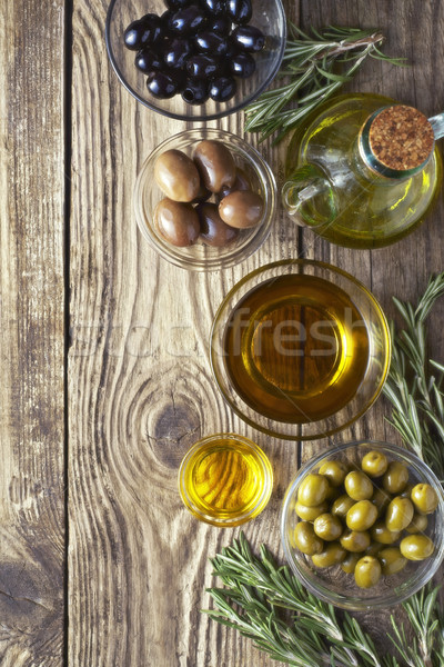 Olives with olive oil and rosemary on the wooden table Stock photo © Karpenkovdenis