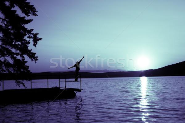Silhouette uomo costa acqua nubi sole Foto d'archivio © kash76