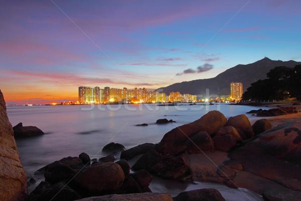 Sunset along seashore with long exposure of sea stones Stock photo © kawing921