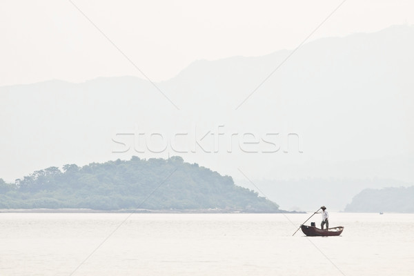 A fisherman on boat alone in the sea, low saturation picture. Stock photo © kawing921