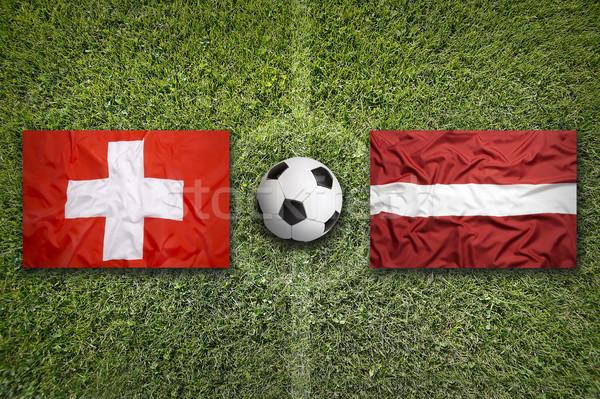 Svizzera vs Lettonia bandiere campo di calcio verde Foto d'archivio © kb-photodesign