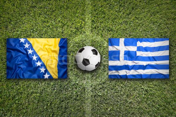 Bosnia Herzegovina vs Grecia banderas campo de fútbol verde Foto stock © kb-photodesign