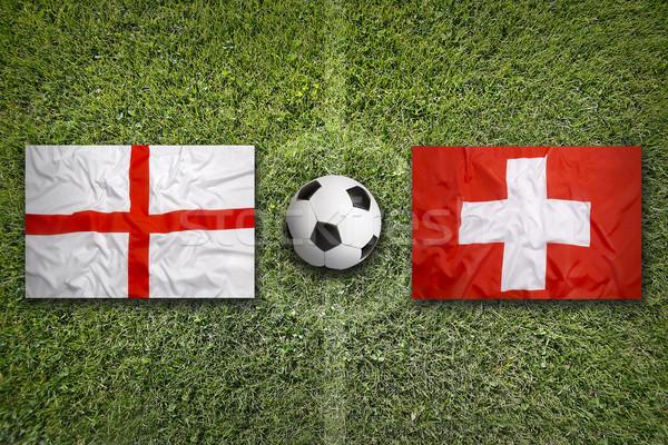 Inglaterra vs Suíça bandeiras campo de futebol verde Foto stock © kb-photodesign