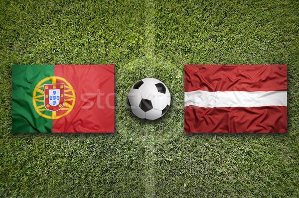 Stock photo: Portugal vs. Latvia flags on soccer field