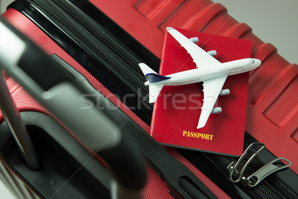 Red passport and airplane model on red luggage Stock photo © kenishirotie