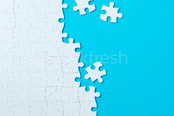 Jigsaw puzzle pieces on blue background Stock photo © kenishirotie