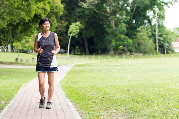 Front view of senior woman jogging through park Stock photo © kenishirotie