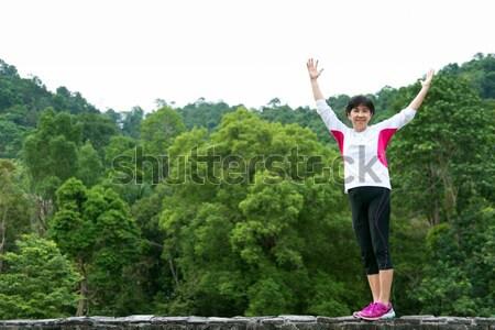 Asian senior woman raise up hand in park Stock photo © kenishirotie