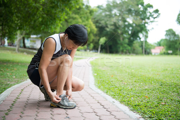Senior jogger tighten her running shoe laces Stock photo © kenishirotie