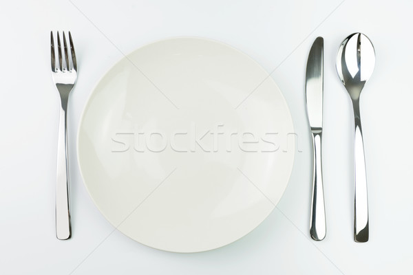 Empty plate with fork, knife and spoon Stock photo © kenishirotie