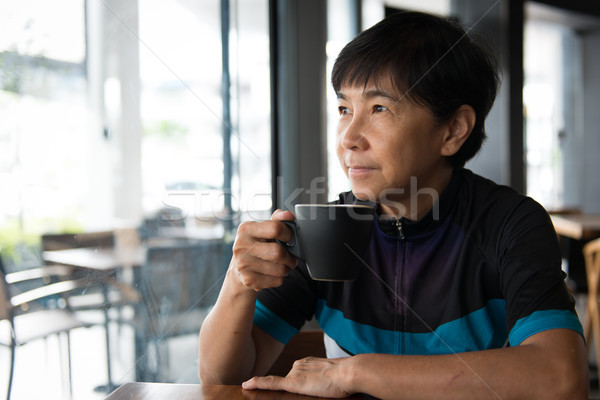 Senior Asian woman with coffee in cycling jersey Stock photo © kenishirotie