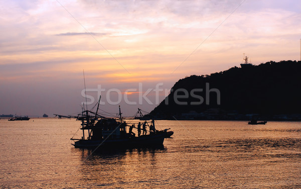 Silhouette of fisherman and boat in the bay during sunset Stock photo © Kheat