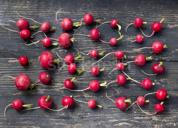 Radishes in line on a black wooden table Stock photo © Kidza