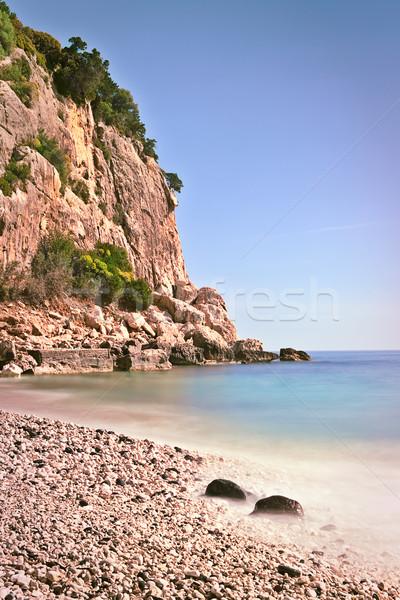 Rocky beach high cliffs blue sea  Stock photo © kikkerdirk