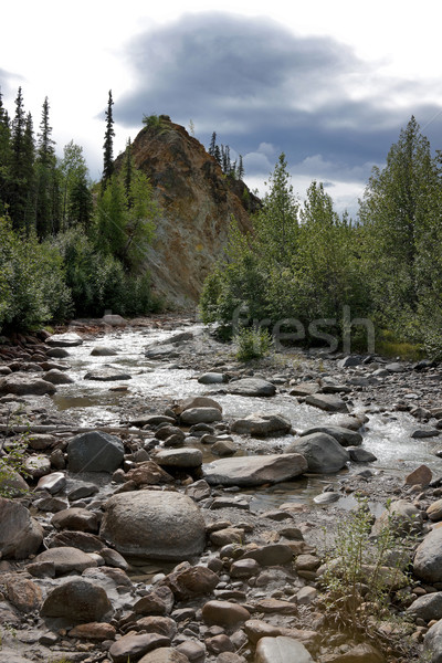 River reduced to narrow flow over boulders under stormy skies in Stock photo © Klodien