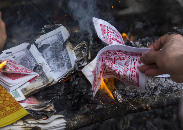 Burning fake dollars and dongs at the temple of One Pillar Pagoda. Stock photo © Klodien